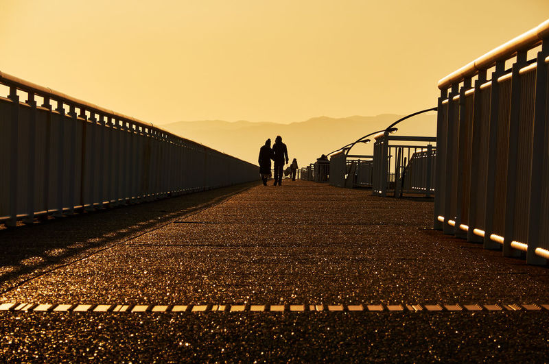 Rear view of people walking on bridge against sky during sunset