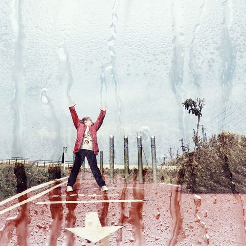 Double exposure image on girl standing on wet footpath and condensed glass