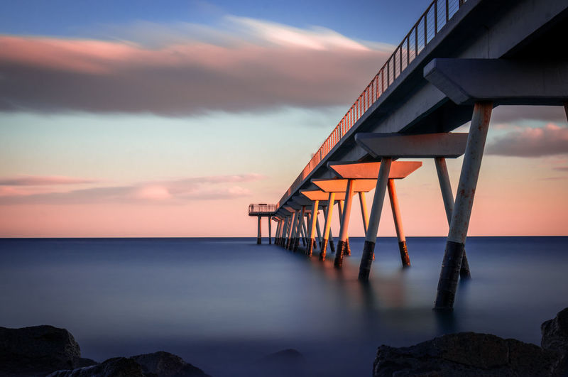 Water Sea Sky Sunset Horizon Scenics - Nature Horizon Over Water Cloud - Sky Beauty In Nature Nature Tranquility Tranquil Scene Dusk No People Orange Color Rock Built Structure Architecture Idyllic Outdoors Pont Del Petroli Pont Del Petroli, Badalona, Spain Long Exposure Clouds Calm Place