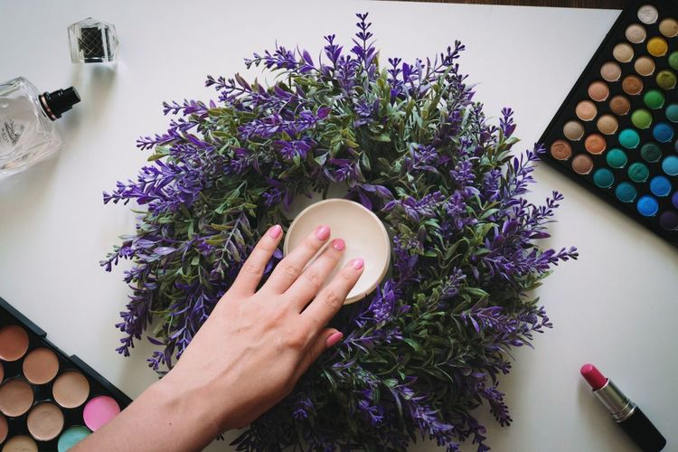 Cropped image of hand touching beauty product