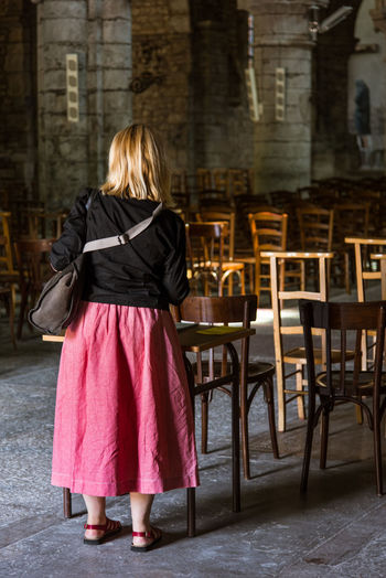 Rear view of woman standing by chairs on floor in church
