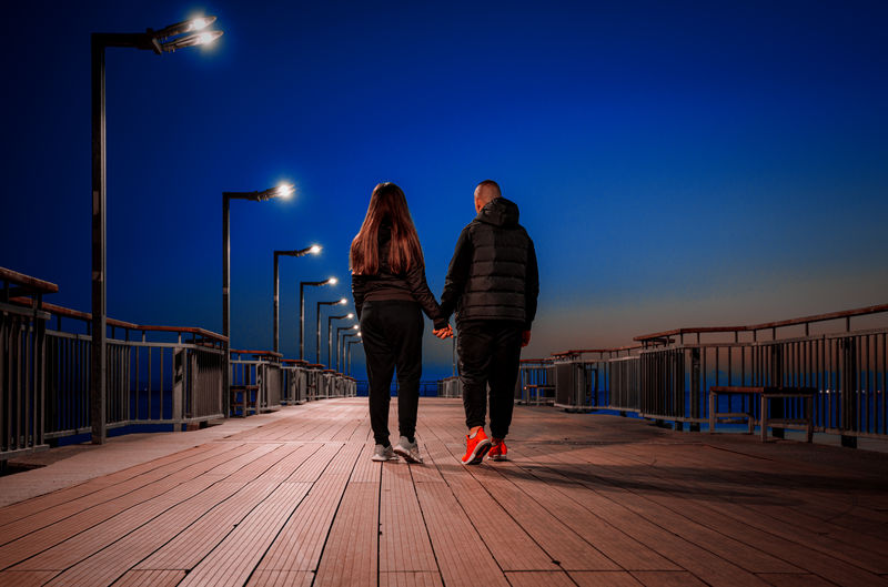 Rear view of people walking on pier against sky