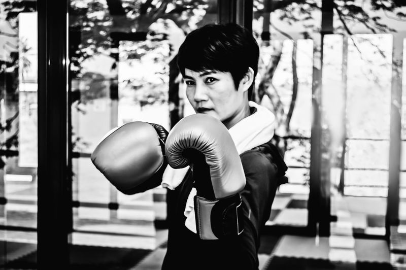 Boxing - Sport One Person Boxing Glove Lifestyles Indoors  Standing Sport Strength Adult Young Adult Real People Focus On Foreground Portrait Waist Up Exercising Looking At Camera Leisure Activity Women Punching Hairstyle Arms Raised Human Arm Beautiful Woman