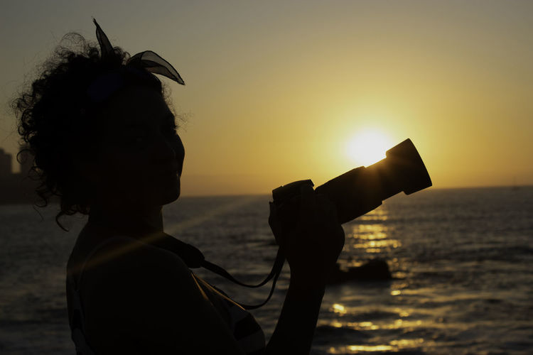Silhouette woman with camera against sea during sunset