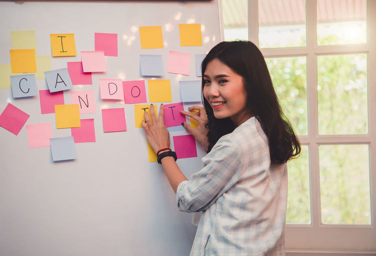 Smiling young woman standing by text over adhesive notes on whiteboard