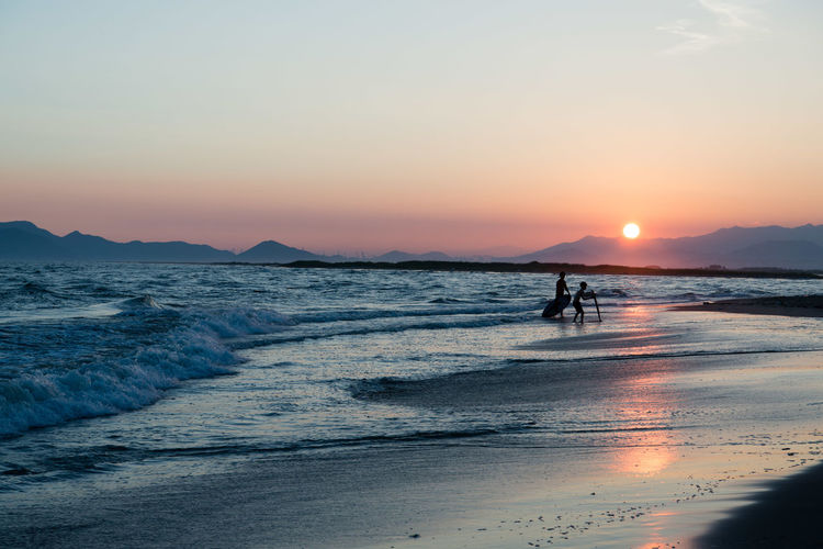 Beach Beauty In Nature Horizon Over Water Idyllic Land Leisure Activity Lifestyles Motion Nature Orange Color Outdoors People Real People Scenics - Nature Sea Silhouette Sky Sun Sunset Two People Water Wave