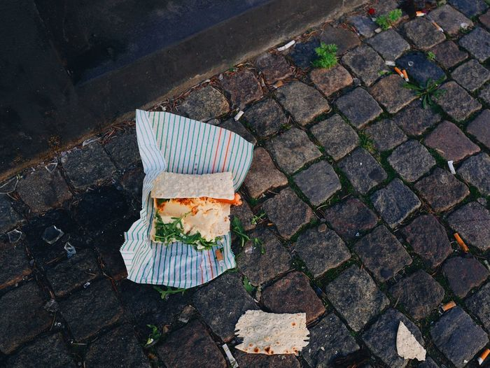High angle view of fallen wrap sandwich on footpath in city