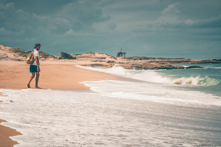 Rear View Of Man On Shore At Beach Against Sky