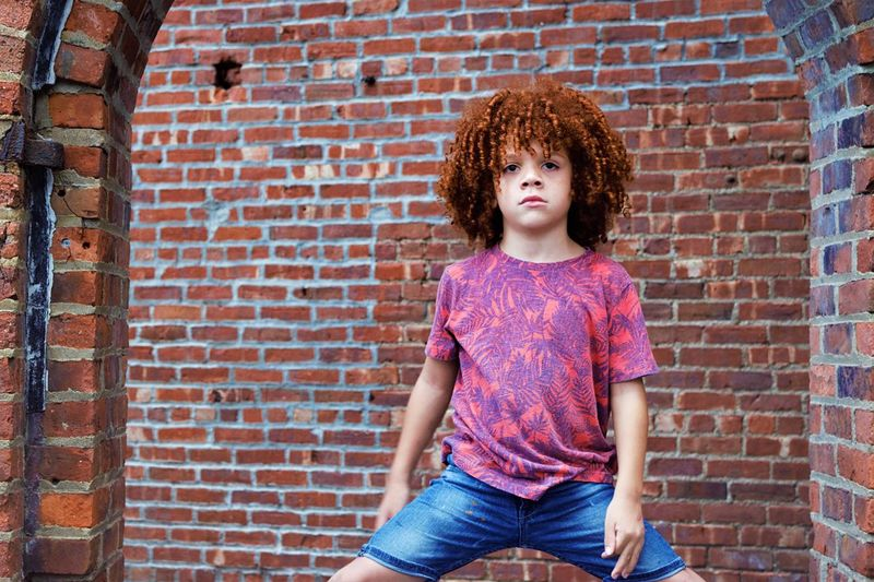 Portrait of boy standing with legs apart against brick wall