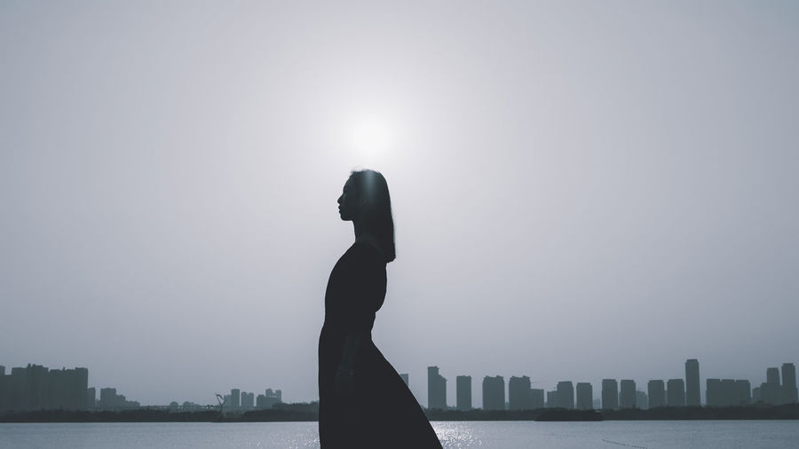 Silhouette of man looking at sea against sky