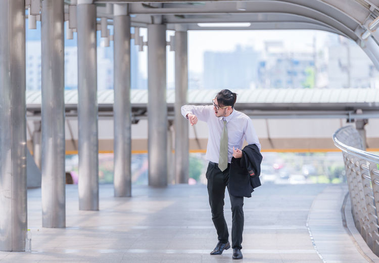 Mid Adult Businessman Checking Time While Walking On Elevated Walkway