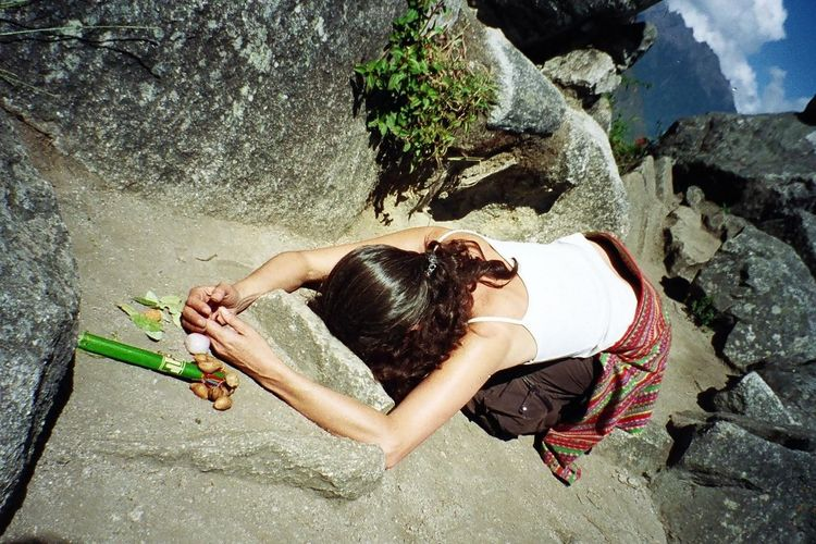Rear view of woman meditating on rock formation at machu picchu