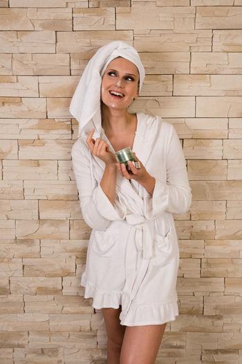 Happy Woman In Bathrobe Holding Face Cream Against Wall