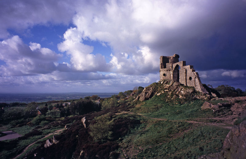 Mow cop castle on mountain against cloudy sky