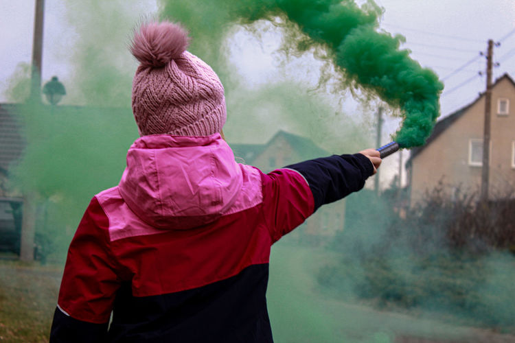 Rear view of girl holding distress flare
