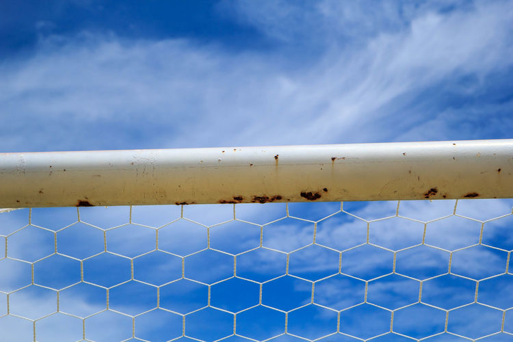 Close-up of metal railing against sky