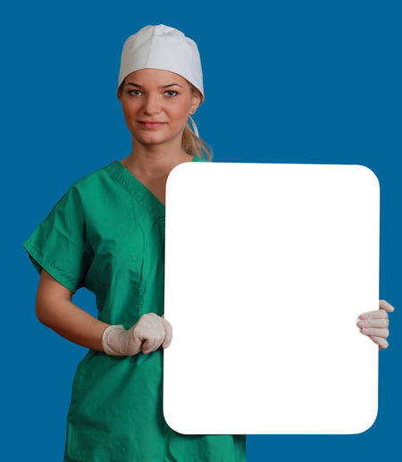 Young woman doctor keeping a white board, against a blue background. Copy Space Doctor  Healthcare Medicine Nurse White Board Blue Blue Background Front View Healthcare And Medicine Holding Keeping Looking At Camera Medical Cannabis Message One Person One Woman Only One Young Woman Only People Physician Placard Portrait Studio Shot Young Adult Young Women
