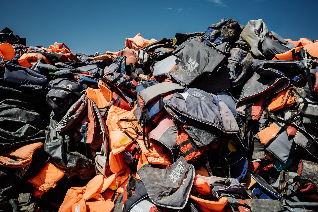Heap of abandoned life jackets against sky