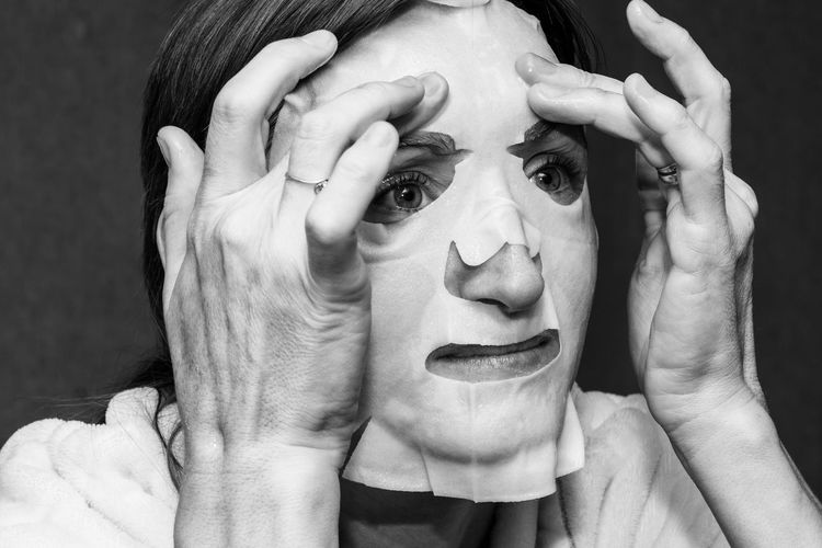 A young woman puts a white moisturising mask on her face