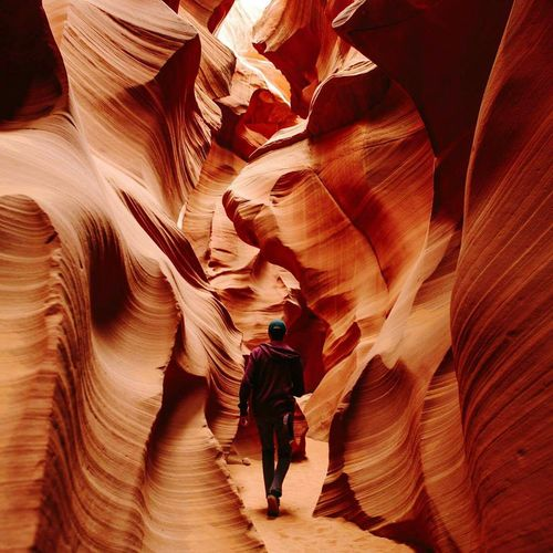Rear View Of Man Walking Amidst Sandstones At Antelope Canyon