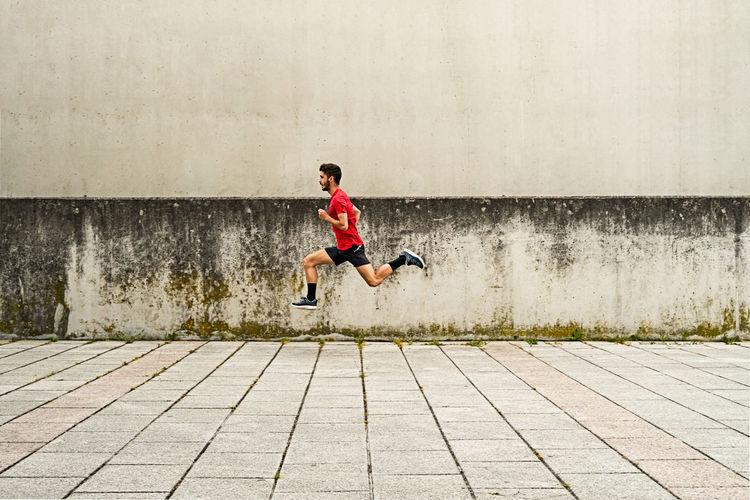 Full length of man running on footpath