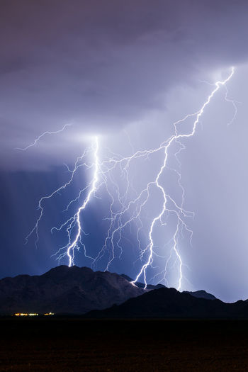 Lightning over silhouette mountains