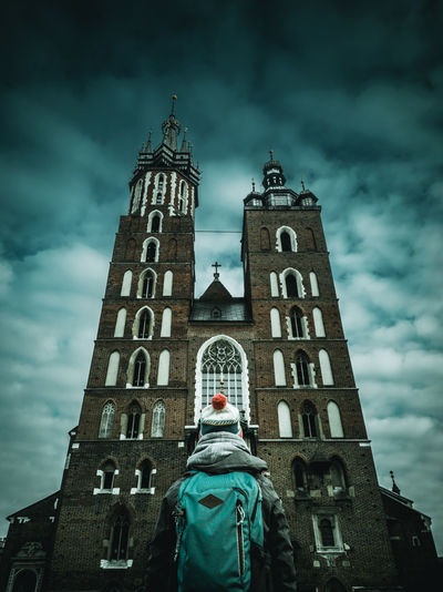 Rear view of mid adult woman with backpack looking at church while standing against cloudy sky