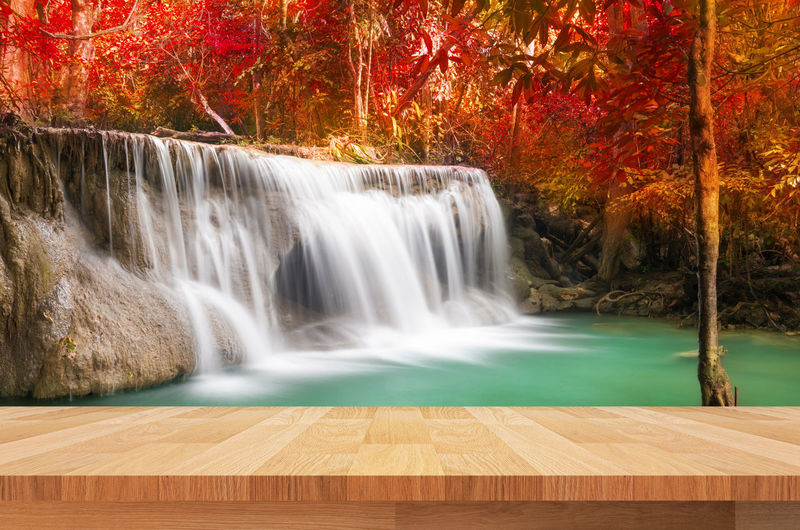 Wooden table against waterfall