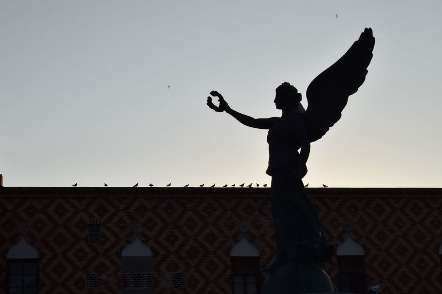 Statue of Nike in Rhodes, Greece Liberty Rhodes Rhodes City Statue Travel Travel Photography Angel Architecture Building Exterior Built Structure City Clear Sky Day Godess Godess Nike Greece Nike Outdoors Silhouette Sky Sunset Winged Statue Wings