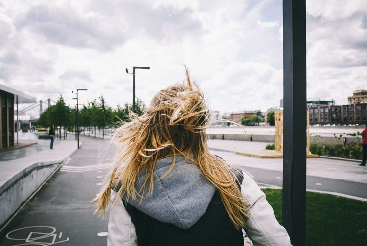 Rear view of a woman walking on road