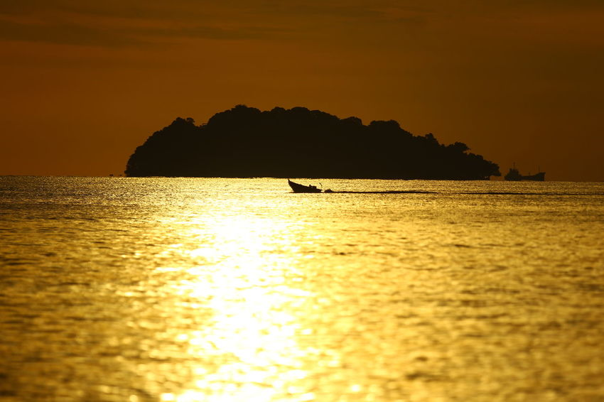 Silhouette objects. Natural yellow cor around the beach in the evening Beauty In Nature Idyllic Mountain Nature Nautical Vessel No People One Animal Orange Color Outdoors Scenics - Nature Sea Silhouette Sky Sunlight Sunset Tranquil Scene Tranquility Water Waterfront
