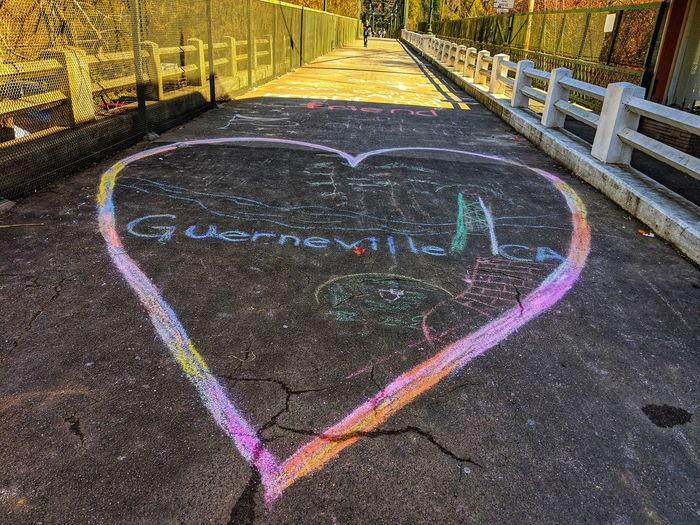 After the Flood. Bridge over food swollen Russian River. Chalk art. Guerneville. Heart Flood Aftermath Love Guerneville Caring Sharing  Loyalty Art Colorful Rainbow Colors Entrance To Bridge Bridge Asphalt Writing Multi Colored High Angle View Street Art Chalk Drawing Graffiti Drawn Drawing Drawing - Activity Smiley Face Road Marking Information Mural Chalk - Art Equipment