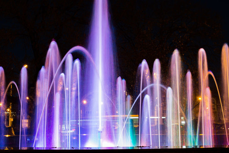 Light trails on fountain in city at night