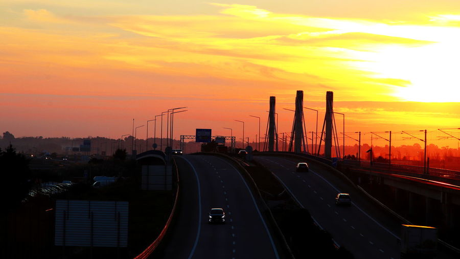 Cars moving on highway against sky during sunset