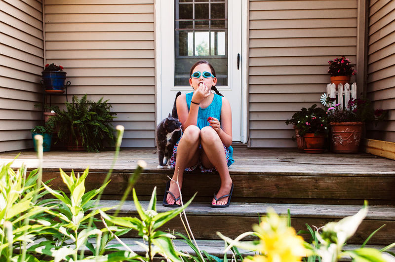 Full Length Portrait Of Woman Sitting On Steps Against House