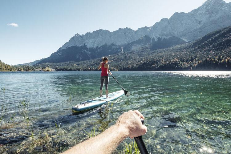 Boy on lake against mountain range