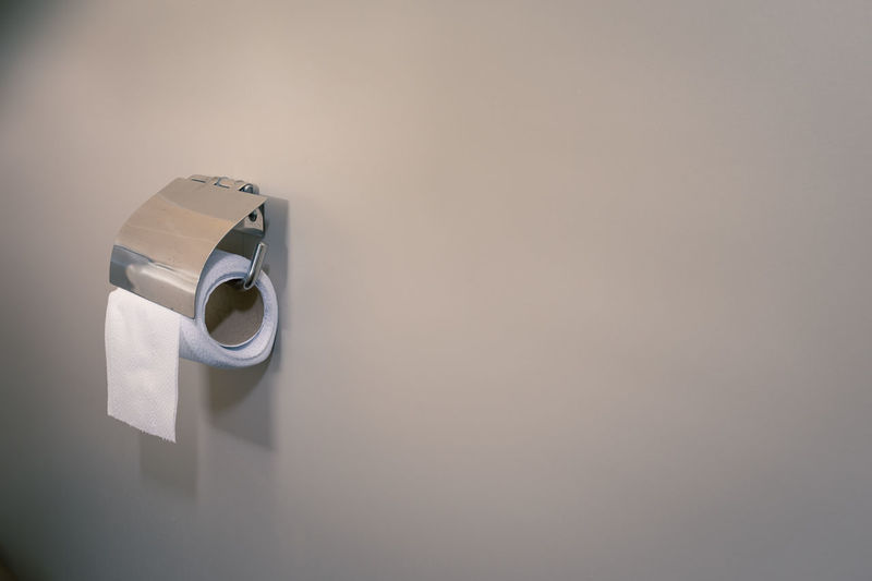Close-up of tissue roll on wall at home
