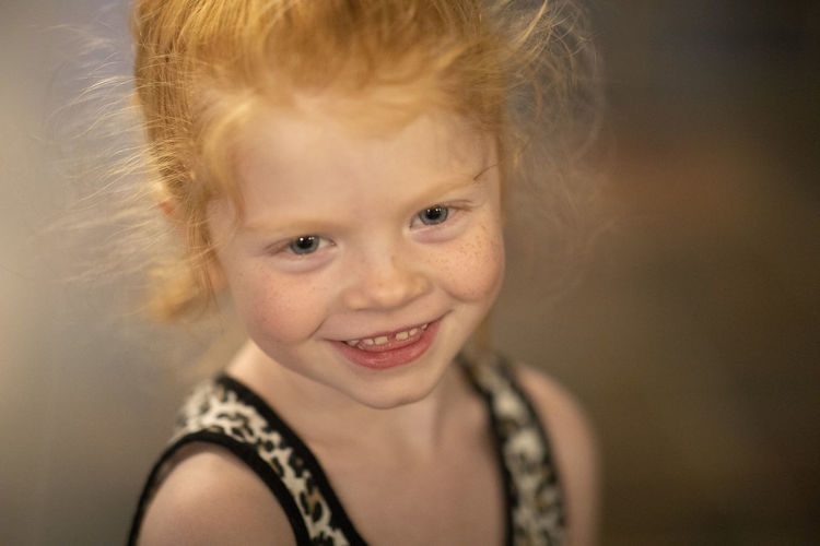 A four-year-old red hair blue eyed girl stands for a portrait. Blue Eyes Red Head Blond Hair Child Childhood Close-up Cute Emotion Females Focus On Foreground Girls Hair Hairstyle Happiness Headshot Human Face Indoors  Innocence Looking At Camera Offspring One Person Portrait Red Hair Smiling