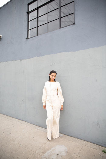 Portrait of young woman standing against gray wall