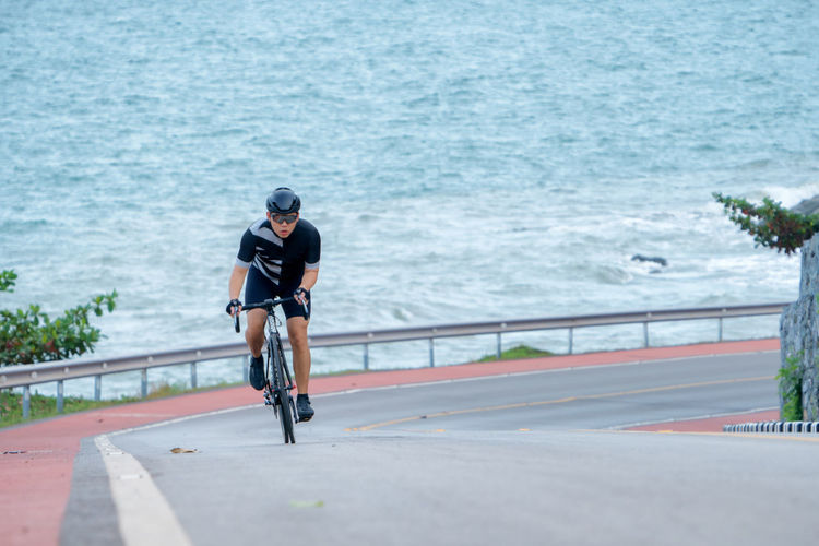 Man riding bicycle on road against sea