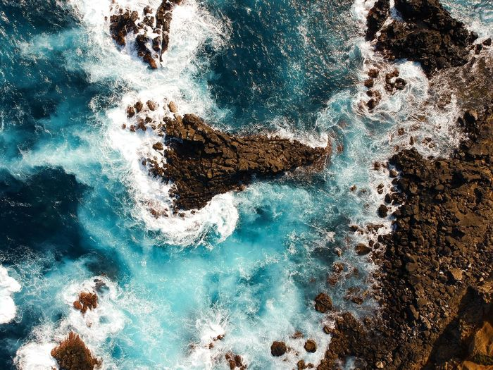 Full frame shot of sea waves splashing on rock