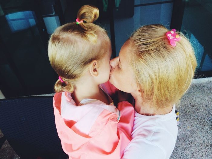 Mother Kissing Daughter While Standing At Home