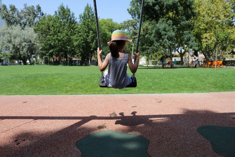 Rear View Of Girl On Swing At The Playground