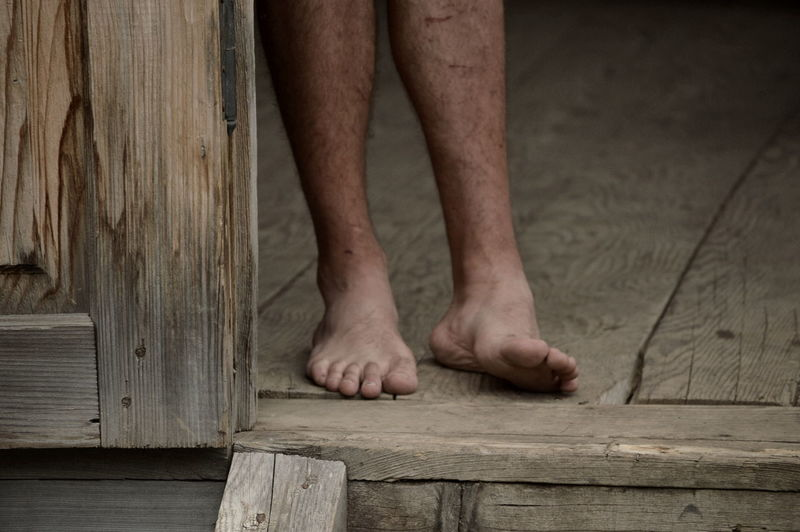 Low section of barefoot man on wooden  floor