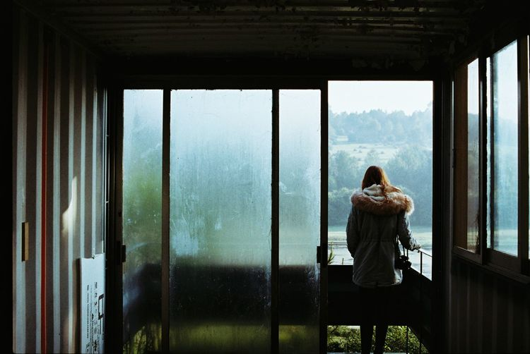 Rear view of woman sitting in glass window