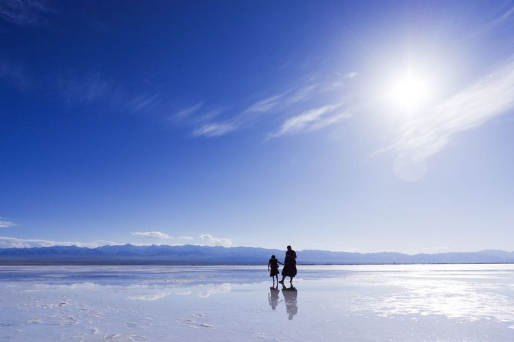 People on salt flat against sky