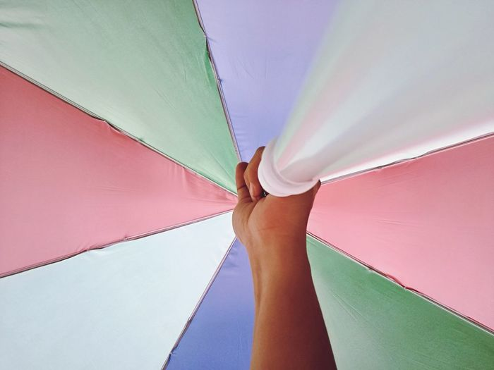 Cropped hand holding colorful umbrella