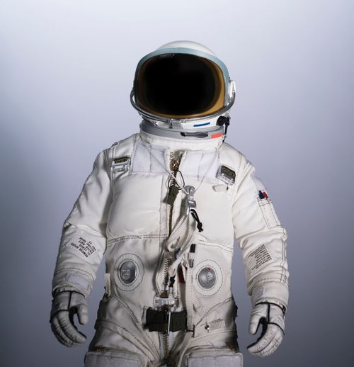 Astronaut wearing uniform while standing against white background