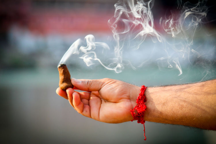 Cropped Hand Of Man Holding Incense