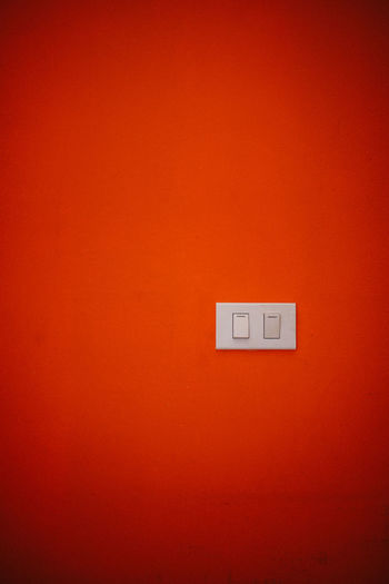 Close-up of switch on red wall